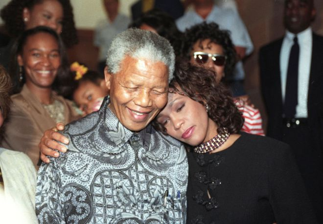 South African President Nelson Mandela hugs Whitney Houston at the presidency on November 10, 1994. Houston is on a three-concert tour in South Africa.  REUTERS/Juda Ngwenya - RTR1HC2A