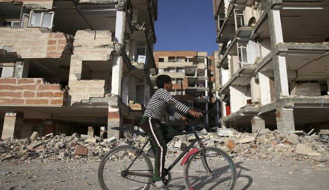 An earthquake survivor rides his bicycle in front of damaged buildings, in a compound which was built under the Mehr state-owned program, in Sarpol-e-Zahab in western Iran, Wednesday, Nov. 15, 2017. Survivors in Iran are awaiting badly needed aid, three days after a powerful earthquake along the Iraq border killed hundreds and left thousands injured. (AP Photo/Vahid Salemi)