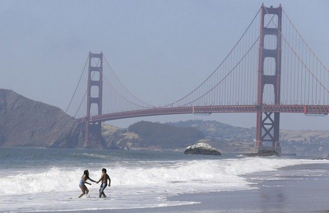 Children play in the surf at Baker Beach with the Golden Gate Bridge shown at rear in San Francisco, Wednesday, June 21, 2017. The first day of summer is going to be a hot one in the San Francisco Bay Area. The National Weather Service has issued an excessive heat warning for the area through Thursday night. (AP Photo/Jeff Chiu)