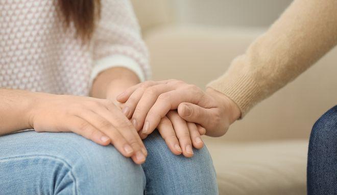 Άνδρας αγγίζει το χέρι γυναίκας.