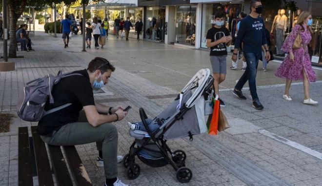 Πολίτες με μάσκα σε εμπορικό δρόμο της Γλυφάδας. Σε ισχύ τα νέα μέτρα.