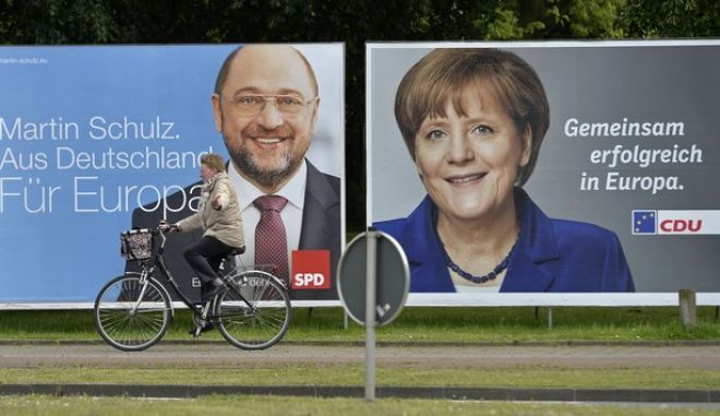 A woman on a bicycle passes election campaign posters for the upcoming elections of the European parliament in Herne, Germany, Tuesday, May 14, 2014. German chancellor Angela Merkel is pictured  for  the Christian Democratic Union (CDU), poster reads : 'Together successful for Europe', poster at left shows  Martin Schulz, president of the European parliament,  for  the German Social Democratic Party  (SPD), poster reads: 'Martin Schulz , From Germany for Europe', . (AP Photo/Martin Meissner)