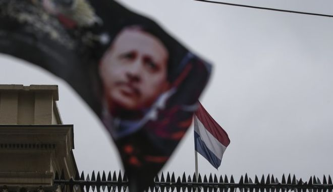 """A banner with a picture of Turkish President Recep Tayyip Erdogan, is waved by protesters outside the Dutch consulate in Istanbul, Sunday, March 12, 2017. Erdogan says he appropriately accused the Dutch government of """"Nazism and fascism,"""" saying only those types of regimes would bar foreign ministers from traveling within their countries. Erdogan also said during a live televised address on Sunday that the Netherlands would """"pay the price"""" for sacrificing its ties with a NATO ally to upcoming elections there. (AP Photo/Emrah Gurel)"""