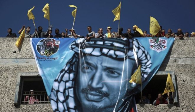 Palestinians wave yellow Fatah movement flags on top of a building with a huge poster of the late Fatah founder and Palestinian Authority leader Yasser Arafat, during a rally marking the 13th anniversary of his death in Gaza City, Saturday, Nov. 11, 2017. (AP Photo/Khalil Hamra)