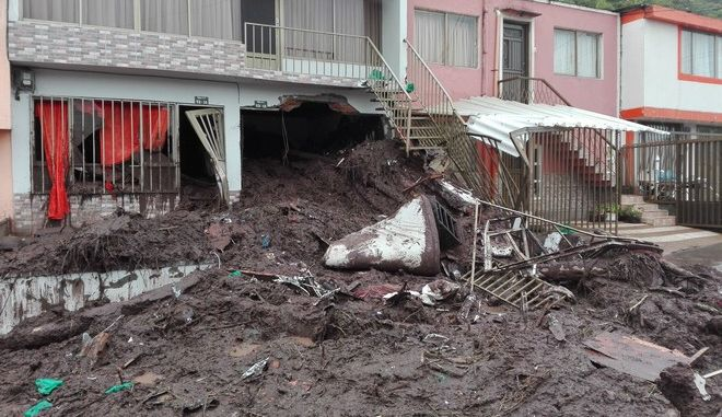 A home is engulfed in mud in Manizales, Colombia, Wednesday, April 19, 2017. At least seven people are dead after intense rains provoked several landslides in a mountainous, coffee-growing part of Colombia. Authorities say the landslides happened early Wednesday after the city received the equivalent of one months rain over the course of a night. (AP Photo/Maria Luisa Garcia)