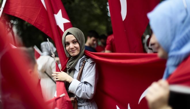 Women attend a demonstration against a coup attempt in Turkey, in front of the Turkish embassy in Berlin, Germany, Saturday, July 16, 2016. Turkish President Recep Tayyip Erdogan told the nation Saturday that his government was working to crush a coup attempt after a night of explosions, air battles and gunfire across the capital. Officials said the coup appeared to have failed as Turks took to the streets overnight to confront troops attempting to take over the country. (AP Photo/Markus Schreiber)