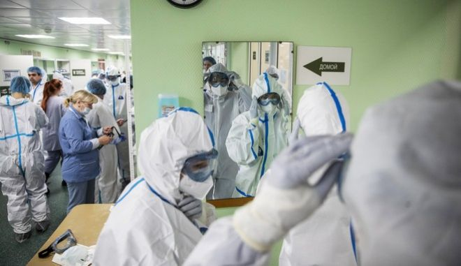 Medical workers put on protective gear before assisting coronavirus patients at the Filatov City Clinical Hospital in Moscow, Russia, Friday, May 15, 2020. Russian capital, with a population of more than 12 million, accounts for half of the country's more than 262,000 reported infections. (AP Photo/Pavel Golovkin)