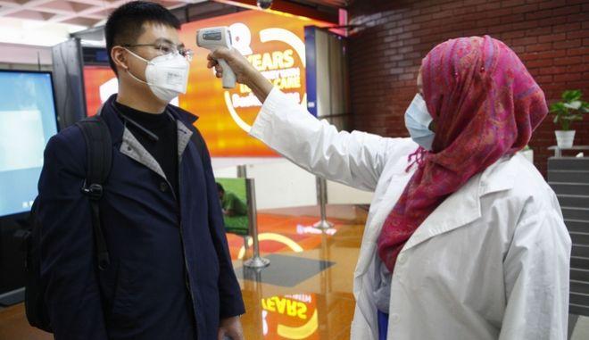 Επιβάτης από το Πεκίνο εξετάζεται καθώς προσγειώθηκε στο Μπαγκλαντές.
