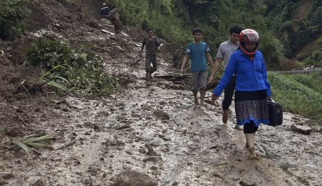 Residents walk through a muddy road which was damaged by a landslide in northern province of Son La, Vietnam on Thursday Oct. 12, 2017. Floods and landslides after a tropical depression have killed over 30 people, and damaged homes and crops in northern and central Vietnam, officials said. (Huu Quyet/Vietnam News Agency via AP)