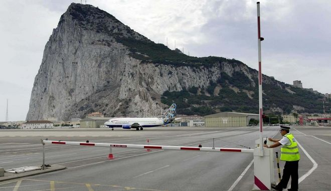 A policeman patrols a road crossing at the Gibraltar airport, Aug. 26, 2001. After nearly three centuries under British rule, the Rock of Gibraltar, synonym for dependability and symbol of the British empire's former invincibility, is tipping back into Spanish hands. (AP Photo/Roca Perales)