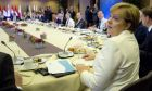 German Chancellor Angela Merkel, right, joins other EU leaders for a breakfast meeting during an EU summit in Brussels on Friday, Oct. 20, 2017. European Union leaders gathered Friday to weigh progress in negotiations on Britain's departure from their club as they look for new ways to speed up the painfully slow moving process. (AP Photo/Virginia Mayo, Pool)