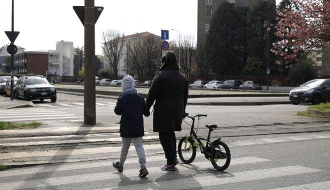 Παιδί περπατά με τη μητέρα του στο Μιλάνο