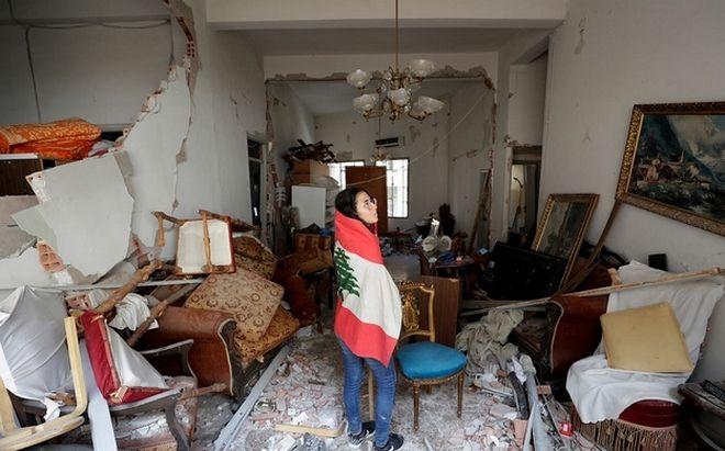 Η Farah Mahmoud, τυλισμένη με τη σημαία του Λιβάνου, κοιτάζει τις ζημιές στο σπίτι των γονιών της.