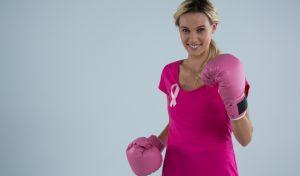 Γυναίκα με γάντια μποξέρ και καρφίτσα με την κορδέλα κατά του καρκίνου του μαστού