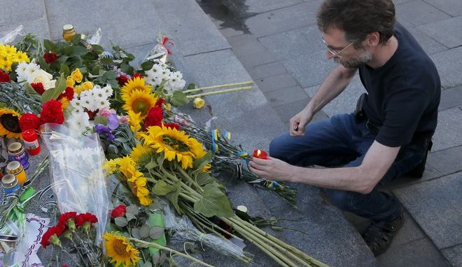 A man lights a candle at a memorial for killed journalist Pavel Sheremet in Kiev, Ukraine, Wednesday, July 20, 2016. Pavel Sheremet, a prominent journalist was killed in a car bombing in Kiev, on Wednesday, sending shockwaves through the Ukrainian journalist community that was shaped by the gruesome killing 16 years ago of the founder of the publication he worked for. (AP Photo/Efrem Lukatsky)
