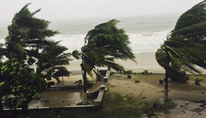 Trees are lashed by strong winds in Sambava, Madagascar Tuesday, March 7, 2017 as heavy rains and strong winds from a cyclone hit northeast Madagascar, raising concerns about flooding and landslides. Aid workers were on alert as Cyclone Enawo lashed the coastline. The storm was expected to move south through the island nation for several days, affecting the capital of Antananarivo along the way. (AP Photo/Manny Horsford)