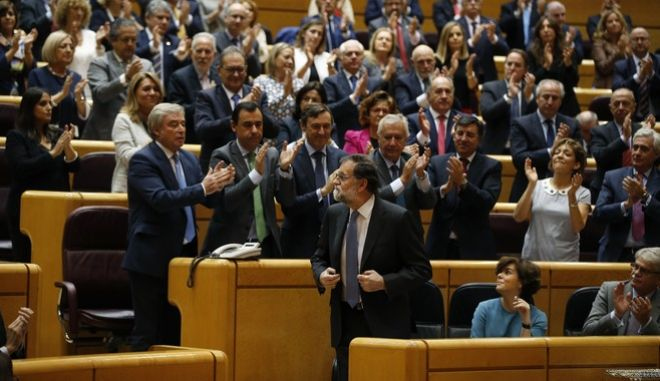 Spain's Prime Minister Mariano Rajoy, centre, is applauded after a speech at the Senate in Madrid, Spain, Friday, Oct. 27, 2017. Rajoy has appealed to the country's Senate to grant special constitutional measures that would allow the central government to take control of Catalonia's autonomous powers to try to halt the region's independence bid. (AP Photo/Paul White)