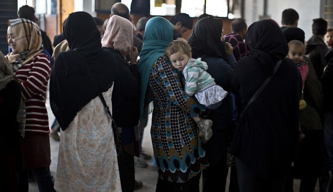 An Afghan refugee child is held by her mother while she and others line up to receive winter coats at the refugee camp of Oinofyta about 58 kilometers (36 miles) north of Athens, Thursday, Jan. 5, 2017. Over 62,000 refugees and migrants are stranded in Greece after a series of Balkan border closures and an European Union deal with Turkey to stop migrant flows. (AP Photo/Muhammed Muheisen)