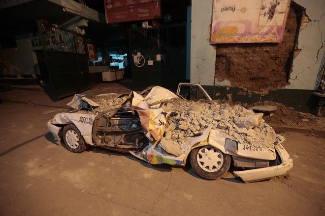 A car stands crushed by rubble after a 7.1 earthquake, in Jojutla, Morelos state, Mexico, Tuesday, Sept. 19, 2017. The earthquake stunned central Mexico, killing more than 100 people as buildings collapsed in plumes of dust. (AP Photo/Eduardo Verdugo)