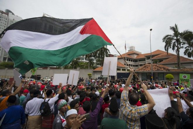 Protesters waves Palestine flags during a protest outside the U.S. Embassy in Kuala Lumpur, Malaysia, Friday, Dec. 8, 2017. Malaysian Muslims, including members of the ruling party, hold protest outside U.S. Embassy over Washington's controversial move to recognize Jerusalem as Israel's capital. (AP Photo/Vincent Thian)