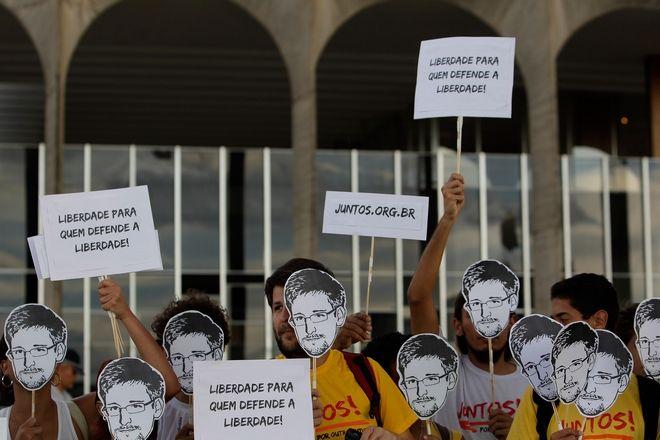 Διαδηλωτές κρατούν εικόνες που απεικονίζουν τον Edward Snowden και αφίσες που γράφουν «Ελευθερία για όσους υπερασπίζονται την ελευθερία», σε διαμαρτυρία μπροστά από το Υπουργείο Εξωτερικών, στη Βραζιλία, 18 Ιουλίου 2013. Οι διαδηλωτές συγκεντρώθηκαν για να δείξουν τη δυσαρέσκειά τους ενάντια στην απόρριψη της αίτησης ασύλου του Snowden από την κυβέρνησή τους.