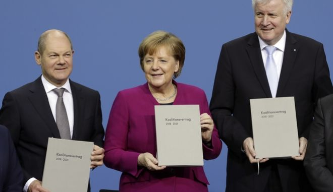 From left, Olaf Scholz, acting chairman of the German Social Democratic Party (SPD), German Chancellor and chairwomen of the German Christian Democratic Union (CDU), Angela Merkel, and the chairman of the German Christian Social Union (CSU), Horst Seehofer, pose with the coalition agreement during a signing ceremony in Berlin, Germany, Monday, March 12, 2018. (AP Photo/Michael Sohn)