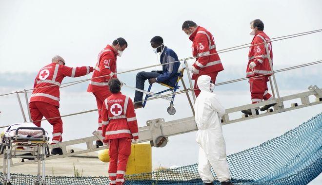 Μετανάστης μεταφέρεται σε  αναπηρική καρέκλα από τους εργαζόμενους του Ερυθρού Σταυρού, στο λιμάνι του Τάραντα της Ιταλίας