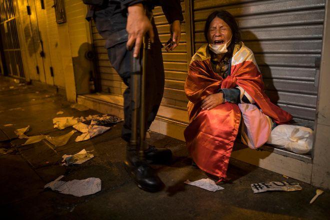 Μια διαδηλώτρια καλυμμένη με περουβιανή σημαία κλαίει από τα δακρυγόνα, 12 Νοεμβρίου 2020.