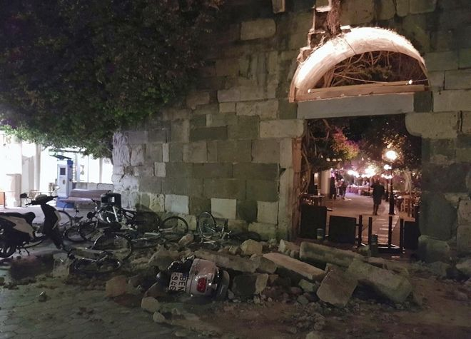 People walk near a damaged building after an strong earthquake on the Greek island of Kos early Friday, July 21, 2017. A powerful earthquake struck Greek islands and Turkey's Aegean coast early Friday morning, damaging buildings and a port and killing people, authorities said. (Kalymnos-news.gr via AP)