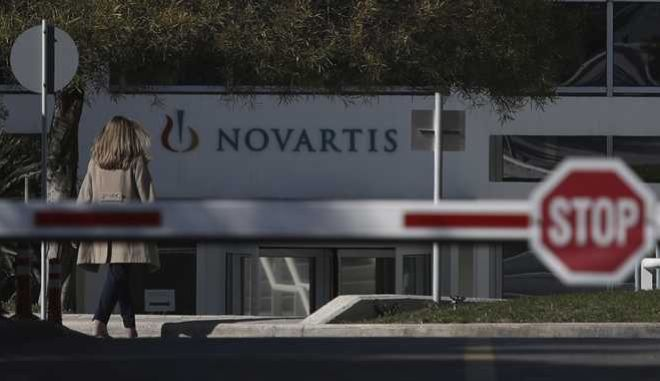 A woman enters Novartis Greek offices in Athens, on Tuesday, Feb. 6, 2018. Greece's government says it has evidence that senior politicians from the previous administration were involved in a bribery case in which Swiss drugmaker Novartis is accused of making illegal payments to fix prices and increase market access.(AP Photo/Petros Giannakouris)