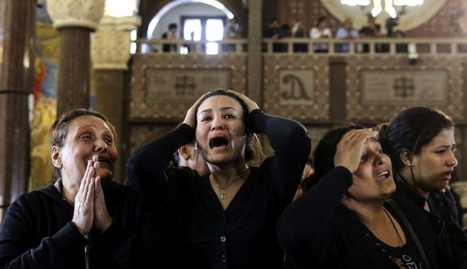 """Women cry during the funeral for those killed in a Palm Sunday church attack in Alexandria Egypt, at the Mar Amina church, Monday, April 10, 2017.  Egyptian Christians were burying their dead on Monday, a day after Islamic State suicide bombers killed at least 45 people in coordinated attacks targeting Palm Sunday services in two cities. Women wailed as caskets marked with the word """"martyr"""" were brought into the Mar Amina church in the coastal city of Alexandria, the footage broadcast on several Egyptian channels. (AP Photo/Samer Abdallah)"""