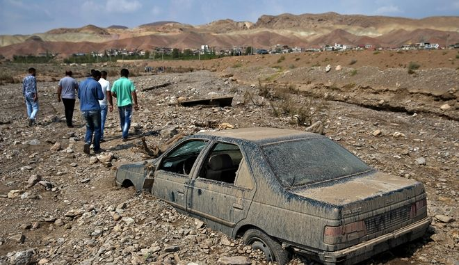 Iranians visit the scene of a flash flood in Pakdasht southeast of the capital Tehran, Iran, Saturday, Sept. 19, 2015. Iran's state TV says flash floods triggered by heavy rains have killed 10 people in the capital, Tehran, and south of the country. Authorities attribute the rising number of deadly flash floods to deforestation and improper construction near riverbeds. (AP Photo/Ebrahim Noroozi)