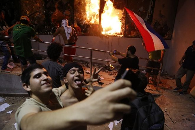 Men pose for a photo outside the congress building during clashes between police and protesters opposing an approved proposed constitutional amendment that would allow the election of a president to a second term, in Asuncion, Paraguay, Friday, March 31, 2017. Some protesters broke through police lines and entered the first floor, where they set fire to papers and furniture. Police used water cannon and fired rubber bullets to drive demonstrators away from the building while firefighters extinguished blazes inside. (AP Photo/Jorge Saenz)