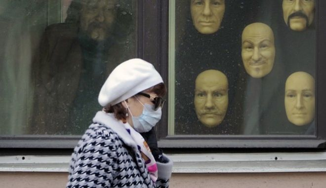 A woman wearing a face mask to protect against coronavirus walks past wax faces displayed in a window of a wax museum in St.Petersburg, Russia, Monday, May 4, 2020. (AP Photo/Dmitri Lovetsky)