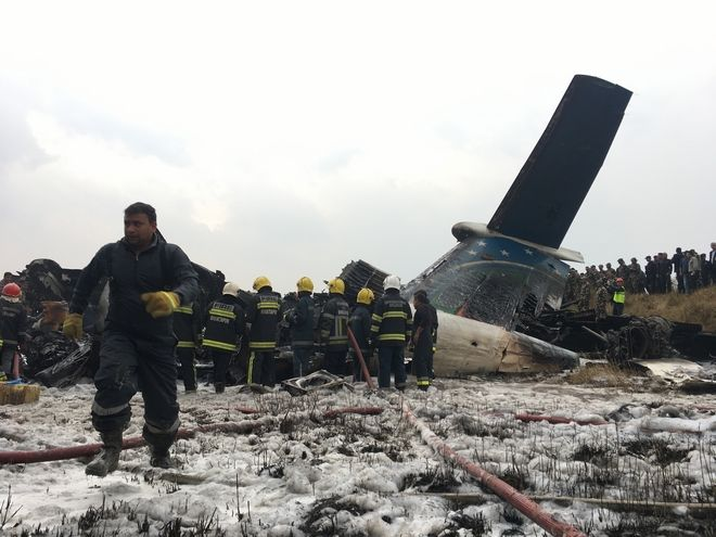 Nepalese rescuers stand near a passenger plane from Bangladesh that crashed at the airport in Kathmandu, Nepal, Monday, March 12, 2018. (AP Photo/Niranjan Shreshta)