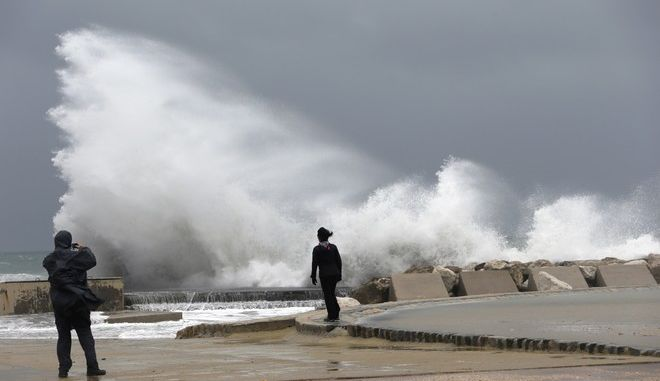 A man photographs waves on the Mediterranean Sea shore in Marseille, southern France, Monday, Dec.11, 2017. Most of the French regions are on alert for violent storms, high winds and high coastal waves. (AP Photo/Claude Paris)