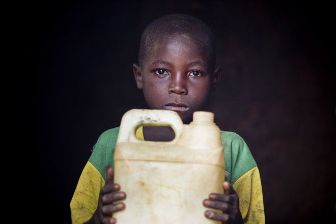 Pascal, 10 years old, holds up his only possession which is a white plastic water container at his home in Buhoro, in  Idjwi Sud, DR Congo Thursday, Sept. 25, 2014