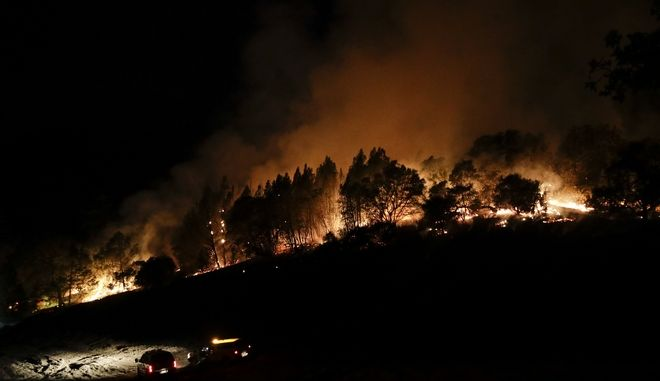 Firefighters watch from their fire trucks as wildfires continue to burn Thursday, Oct. 12, 2017, near Calistoga, Calif. Some of the state's most historic tourist sites, including Sonoma city and Calistoga in Napa Valley, were ghost towns populated only by fire crews trying to stop the advancing infernos. (AP Photo/Jae C. Hong)