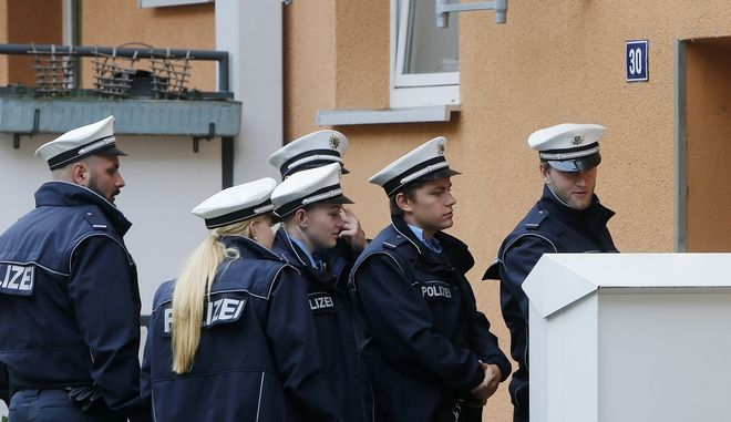 Police officers stand in front of a house when checking door to door during an evacuation of more than 60 000 people in Frankfurt, Germany, Sunday, Sept. 3, 2017. The evacuation became necessary due to an unexploded 1.8 ton WW II bomb that will be diffused later the day. (AP Photo/Michael Probst)