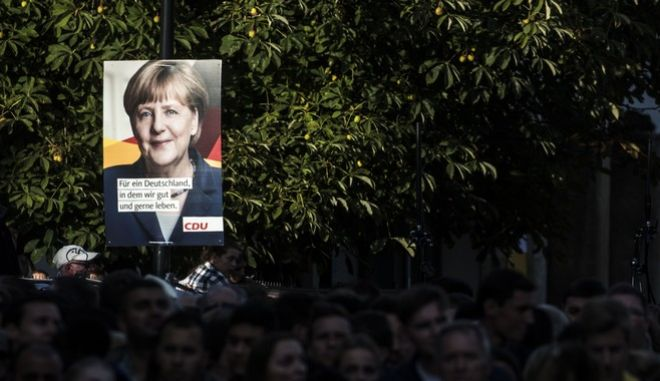 "Numerous spectators stand under a poster of German Chancellor Angela Merkel during an election campaign event in Giessen, central Germany, Thursday Sept. 21, 2017. Slogan on the poster reads ""For a Germany where we live good and enjoy it"". (Frank Rumpenhorst/dpa via AP)"