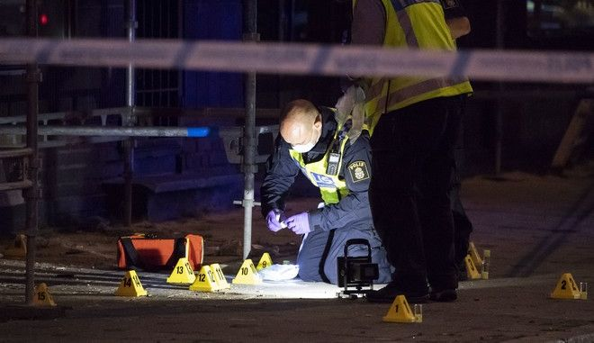 Police forensics investigate the scene after people were shot and injured outside an Internet Cafe in Malmo, southern Sweden, Monday, June 18, 2018.  Swedish police say several people were injured when shots were fired Monday in Malmo, Sweden's third-largest city. (Johan Nilsson/TT News Agency via AP)