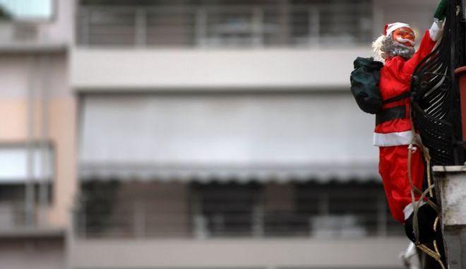 Εορταστικός στολισμός με ομοίωμα Αγίου Βασίλη να σκαρφαλώνει σε μπαλκόνι πολυκατοικίας στην πόλη των Τρικάλων