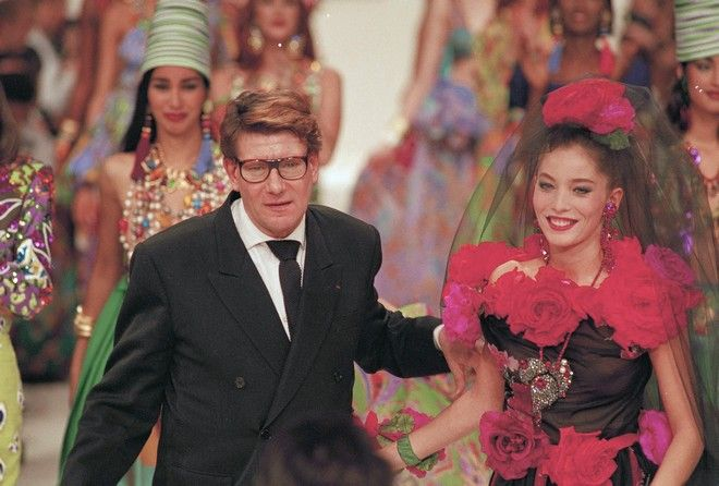 French designer Yves Saint Laurent and a model present his black and red rose adorned bride's dress as they acknowledge applause at the end of his 1991 Spring ready-to-wear collection in Paris, France October 24, 1990.  Model's bridal gown is black adorned with red and fuchia silk flowers.  (AP Photo/Pierre Gleizes)