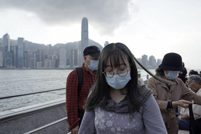 Τουρίστες φορούν προστατευτικές μάσκες προσώπου κατά μήκος της προκυμαίας του Χονγκ Κονγκ, την Πέμπτη 23 Ιανουαρίου 2020