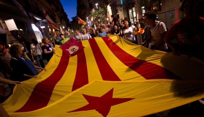 """In this photo taken on Sunday Sept. 10, 2017, people demonstrate carrying """"esteladas"""" or independence flags ahead of the Catalan National Day in Barcelona, Spain, Sunday Sept. 10, 2017. A confrontation between the central government in Madrid and independence movements in the wealthy northeastern Catalonia region has been gripping Spain for weeks. The conflict is due to come to a head on Sunday Oct. 1, 2017 when Catalonia intends to hold a regional ballot on whether to break away from the rest of Spain, despite government efforts to stop a vote being held. (AP Photo/Emilio Morenatti)"""