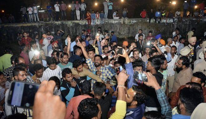 Εξαγριωμένο πλήθος φωνάζει συνθήματα στο σημείο του σιδηροδρομικού δυστυχήματος