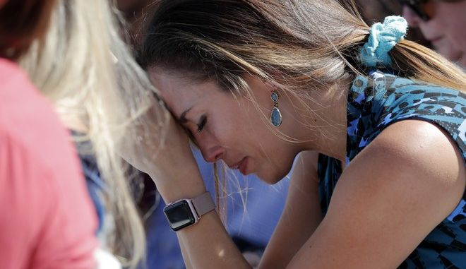 A woman cries as she bows her head in prayer during a vigil at the Parkland Baptist Church, for the victims of the Wednesday shooting at Marjory Stoneman Douglas High School, in Parkland, Fla., Thursday, Feb. 15, 2018. Nikolas Cruz, a former student, was charged with 17 counts of premeditated murder on Thursday. (AP Photo/Gerald Herbert)