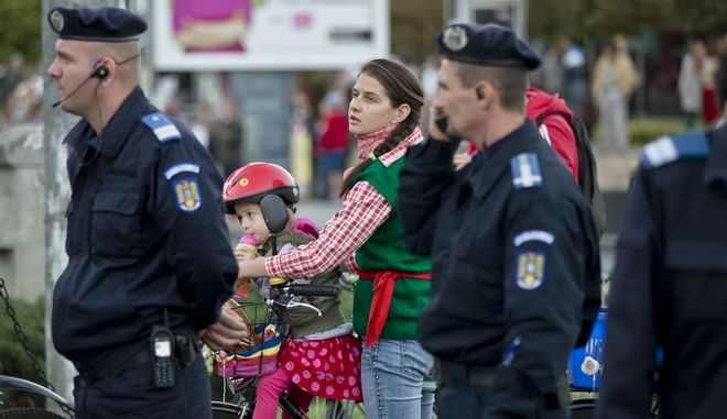 A woman waits along with a baby next to riot policemen at the beginning of a protest march in Bucharest, Romania, Sunday, Sept. 22, 2013. More than 15.000 people joined protests in several Romanian cities, according to local media and police sources, against a planned cyanide extraction based Canadian run gold mine supported by the government. The gold mine, planned to open in the Transylvanian town of Rosia Montana, would be the biggest in Europe. (AP Photo/Vadim Ghirda)