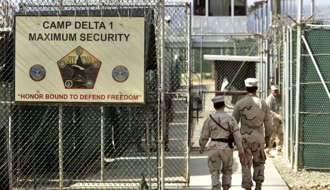 "FILE - In this June 27, 2006 file photo, reviewed by a U.S. Department of Defense official, U.S. military guards walk within Camp Delta military-run prison, at the Guantanamo Bay U.S. Naval Base, Cuba. Attorney General Jeff Sessions is visiting Guantanamo Bay on Friday in a show of support for the prison he has called a ""perfectly acceptable"" place to detain new terrorism suspects, as opposed to holding them in the U.S. and having his own Justice Department try them in civilian courts. (AP Photo/Brennan Linsley, File)"
