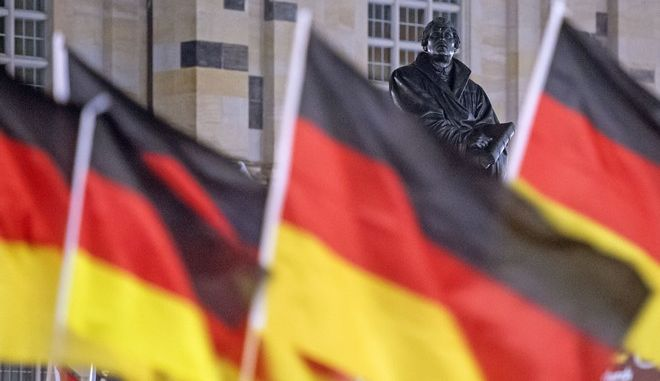 German flags wave besides the Martin Luther Memorial during a rally called 'Patriotic Europeans against the Islamization of the West' (PEGIDA) in front of the Frauenkirche cathedral (Church of Our Lady) while the exterior lighting was switched off during a demonstration in Dresden, eastern Germany, Monday, Feb. 9, 2015. (AP Photo/Jens Meyer)